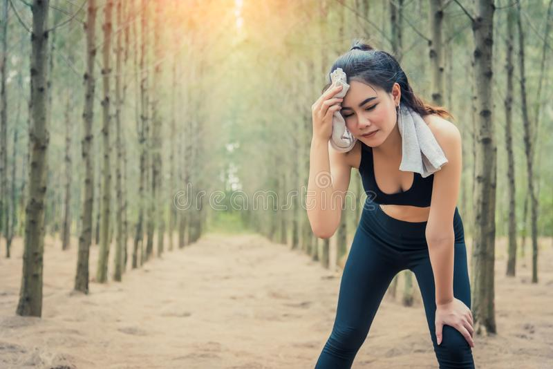 Asian beauty woman wiping the sweat in forest. Towel and sweat elements. Sport and Healthy concept. Jogging and Running concept. royalty free stock photos