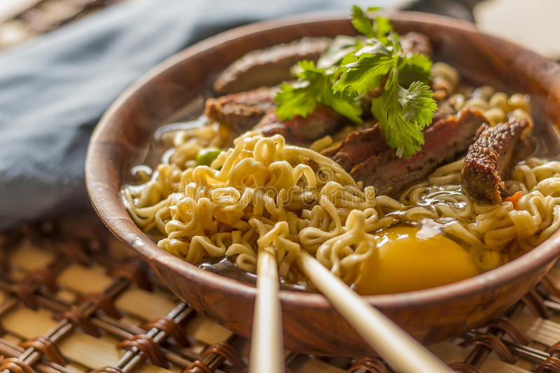 Asian Beef Ramen. Beef ramen served Asian style. Raw egg cooks in steaming hot savory broth royalty free stock photo