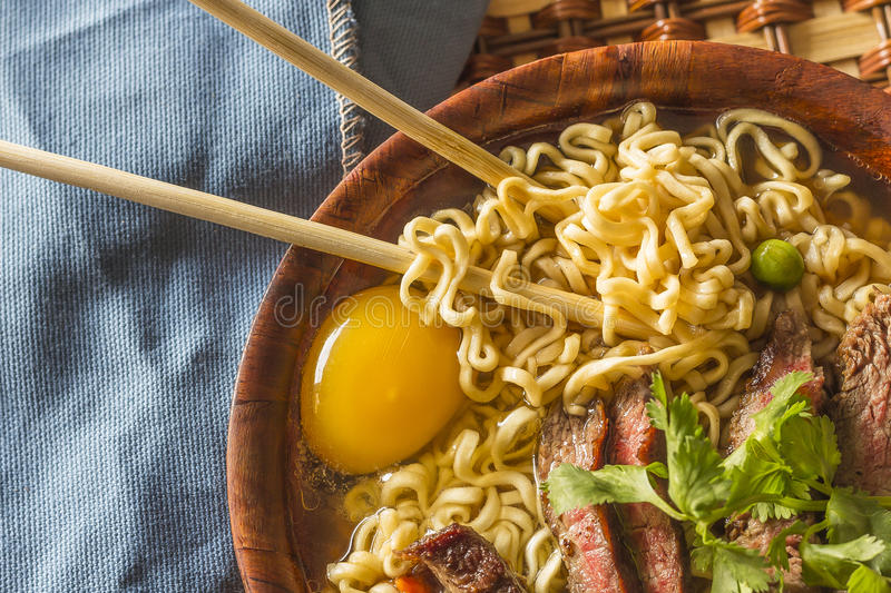 Asian Beef Ramen. Beef ramen served Asian style. Raw egg cooks in steaming hot savory broth stock photography
