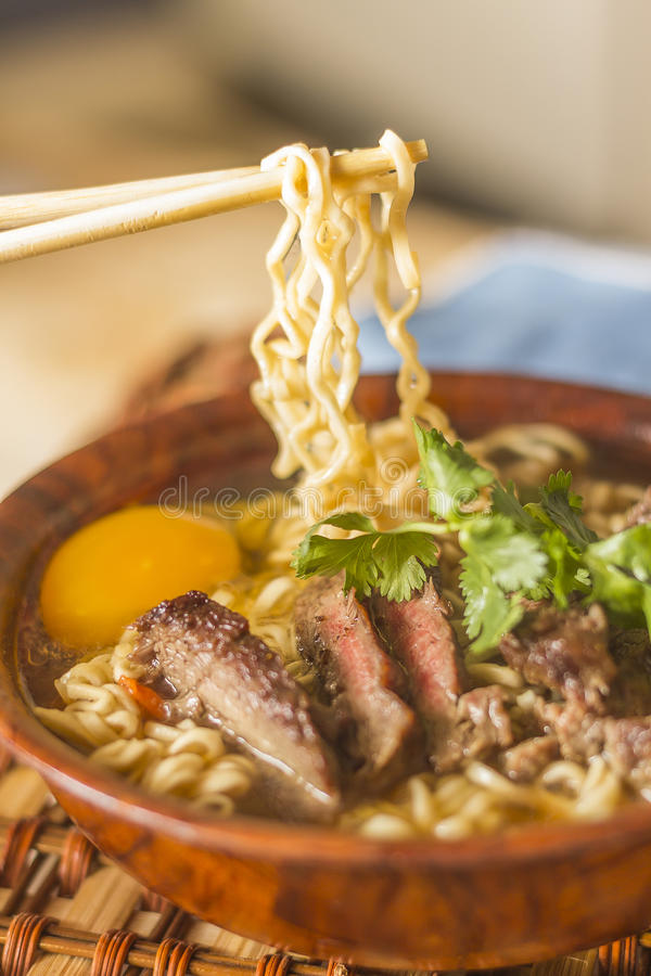 Asian Beef Ramen. Beef ramen served Asian style. Raw egg cooks in steaming hot savory broth royalty free stock image