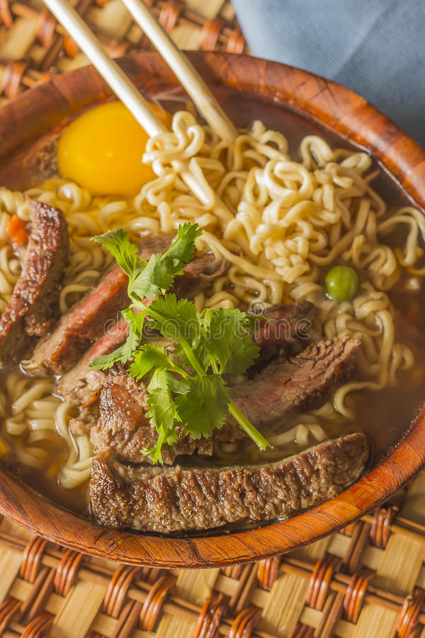 Asian Beef Ramen. Beef ramen served Asian style. Raw egg cooks in steaming hot savory broth royalty free stock photos