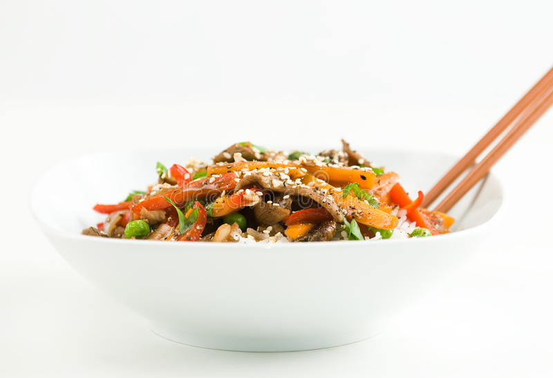 Asian Beef Stir-Fry. On rice with peppers carrots onions and peas in black bean sauce stock image