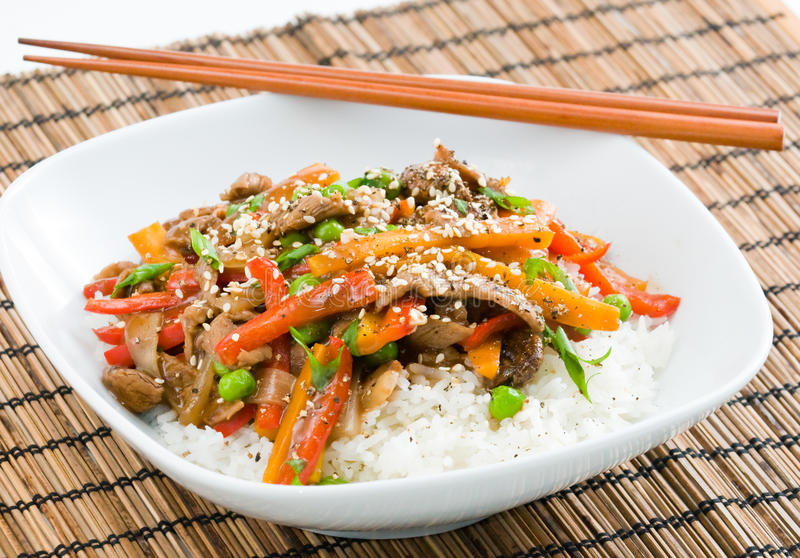 Asian Beef Stir-Fry. On rice with peppers carrots onions and peas in black bean sauce royalty free stock photos