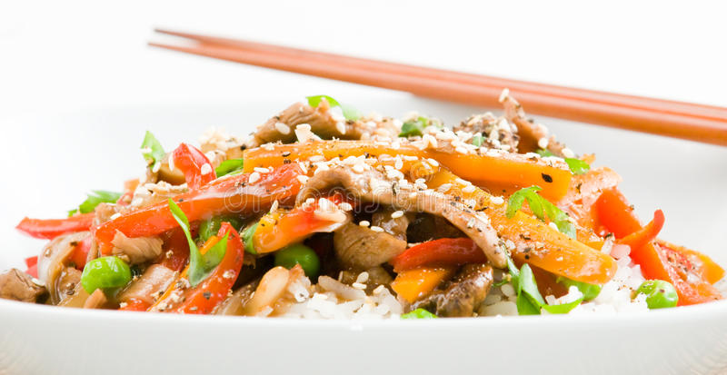 Asian Beef Stir-Fry. On rice with peppers carrots onions and peas in black bean sauce stock photos