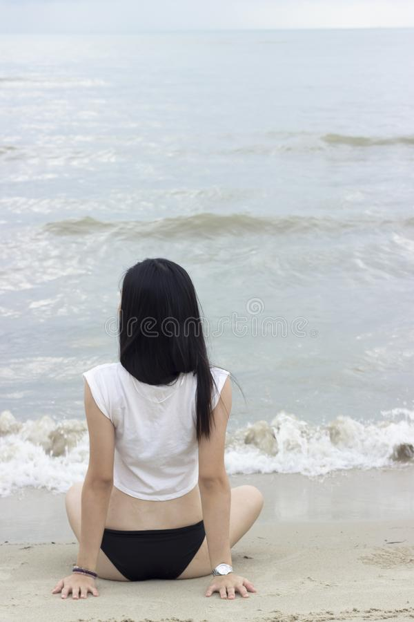 Asian bikini girl sitting at the beach stock image