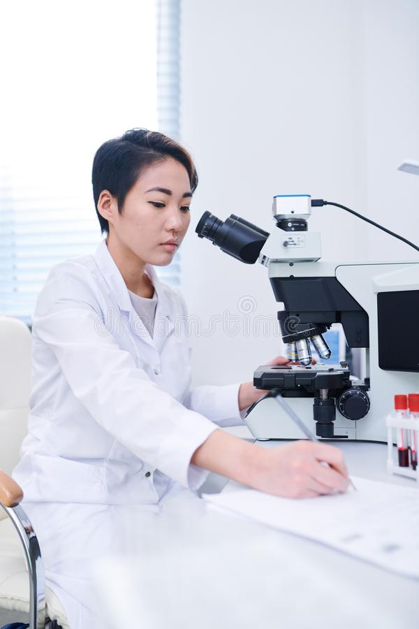 Asian biologist studying cells with microscope royalty free stock image