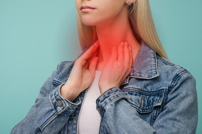 Asian blond woman has thyroid cancer and sore throat. Isolated over blue background stock photo