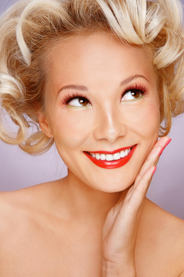 Asian blonde. Beautiful blond smiling asian girl with stylish make-up and hairdo looking upwards with curious expression royalty free stock photo