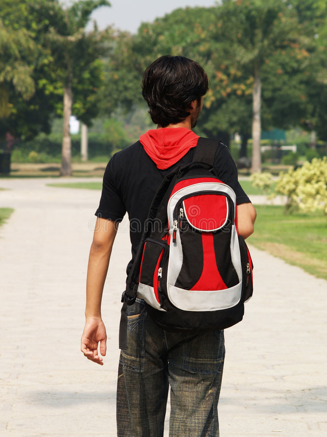 Asian boy carrying backpack stock photo