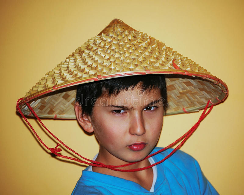 Asian boy with the chinese conical bamboo hat. A 10 year old asian boy wearing a conical chinese bamboo stares with an intense look of determination stock photos