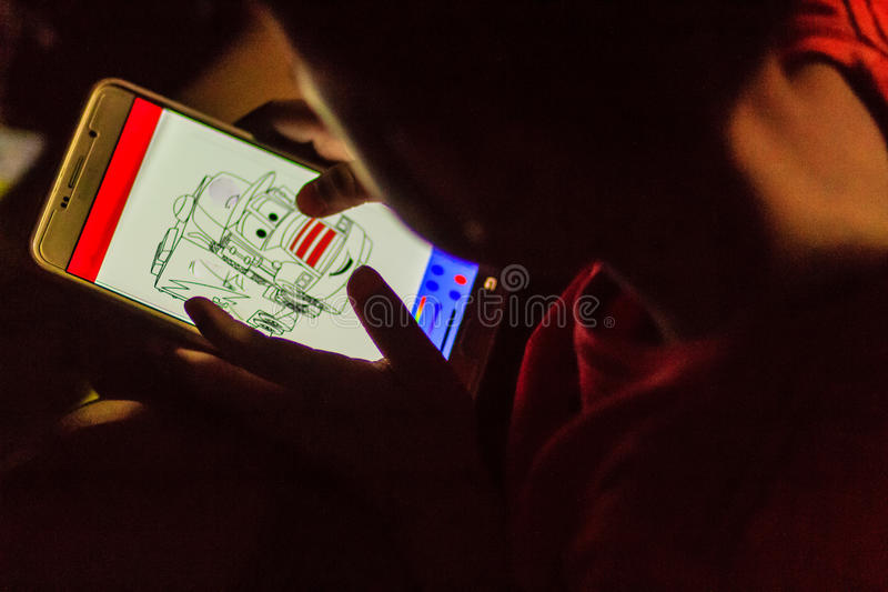 Asian boy is concentrate to drawing with mobile phone application in the dark night. Eyes care concept. Shot with high ISO with n. Oise grain stock photo