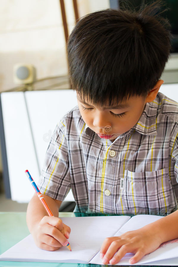 Asian boy doing homework. Writing on a book royalty free stock images