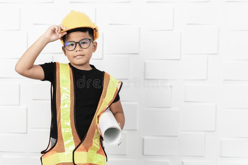 Asian boy dressed as an engineer holding a blueprint stock image