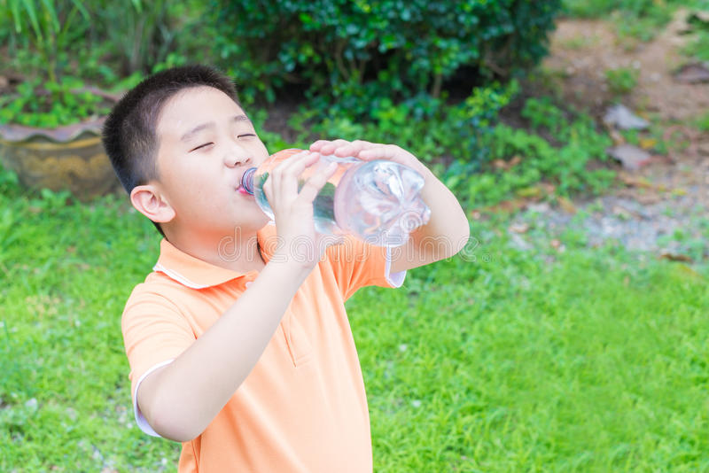 Asian boy drinking water from bottle royalty free stock image