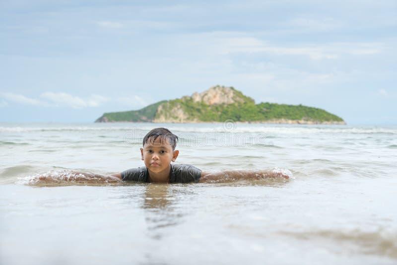 Asian boy enjoying in the sea near the beach at Ao Manao, Prachuap Khiri Khan, Thailand in the afternoon. stock photos