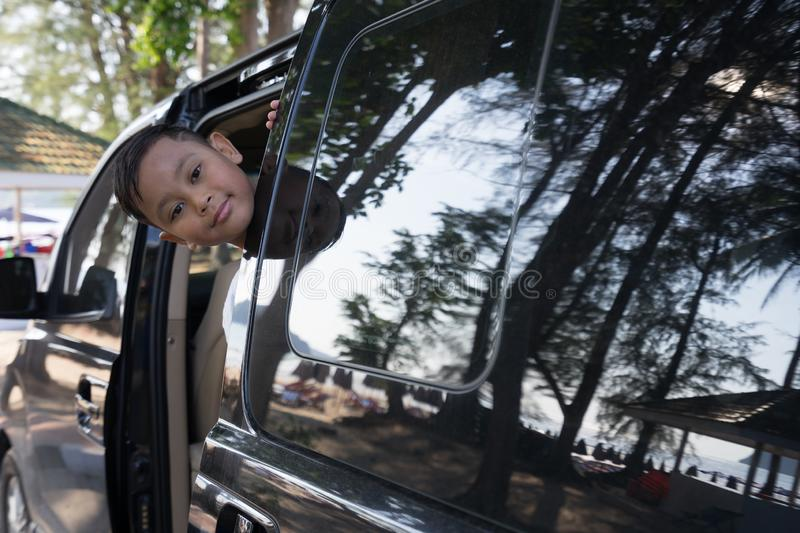Asian boy extends his face out of the car Which parked by the sea.  stock photography