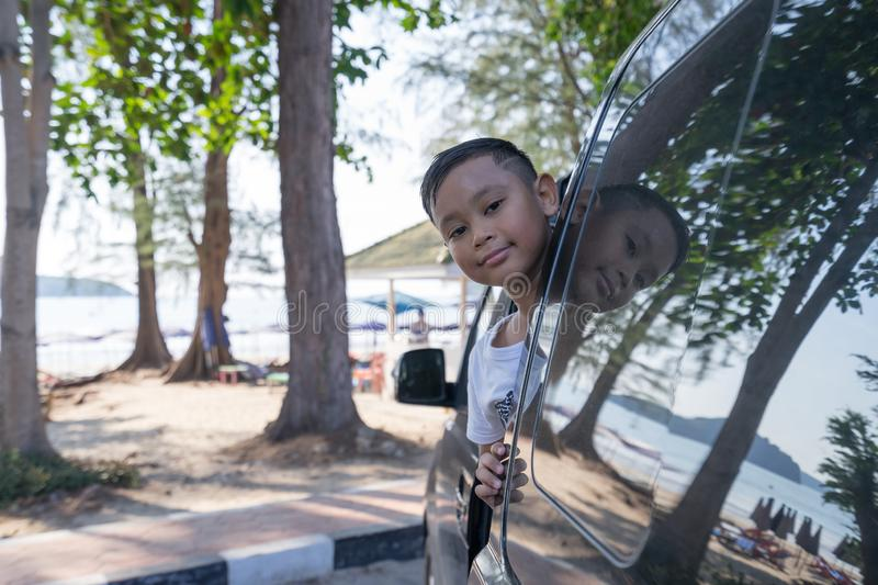 Asian boy extends his face out of the car Which parked by the sea.  royalty free stock photos
