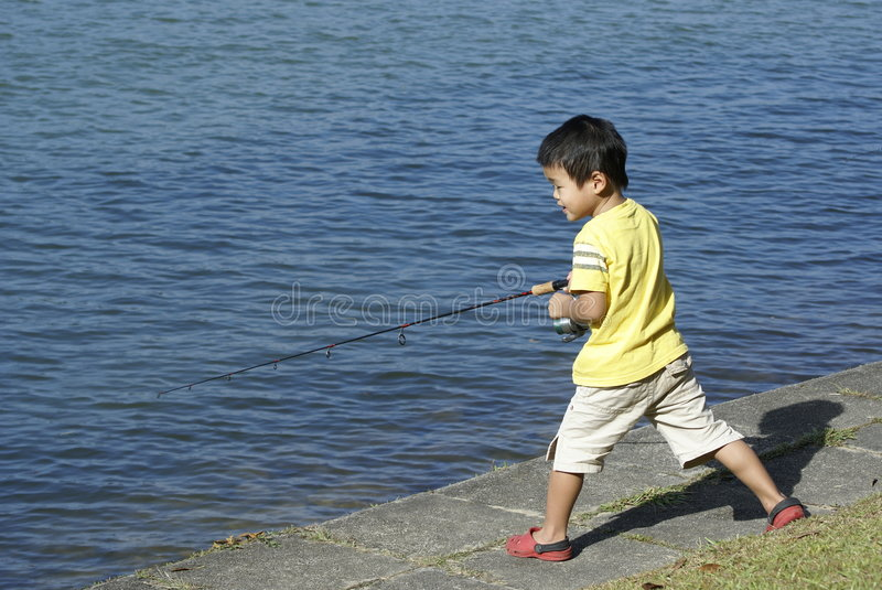 Asian boy fishing. At water's edge stock photography