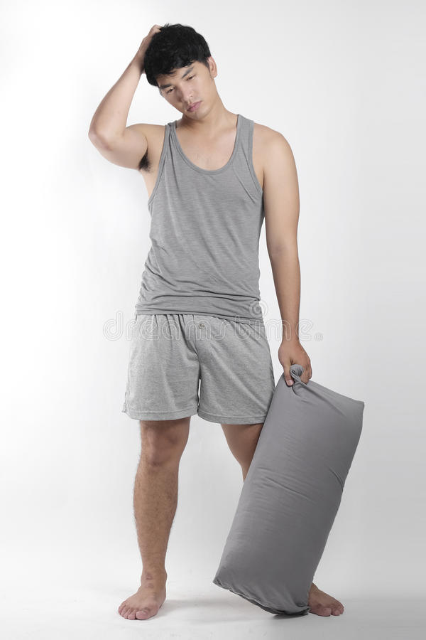 Asian boy in gray pajamas with a pillow royalty free stock photo