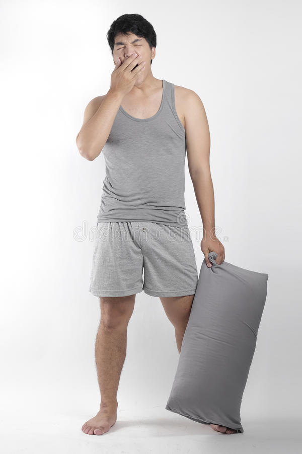 Asian boy in gray pajamas with a pillow royalty free stock images