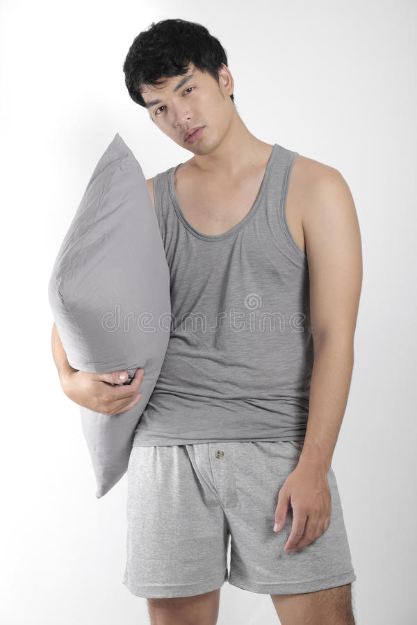 Asian boy in gray pajamas with a pillow stock image
