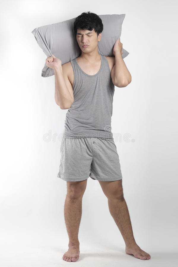 Asian boy in gray pajamas with a pillow royalty free stock photography