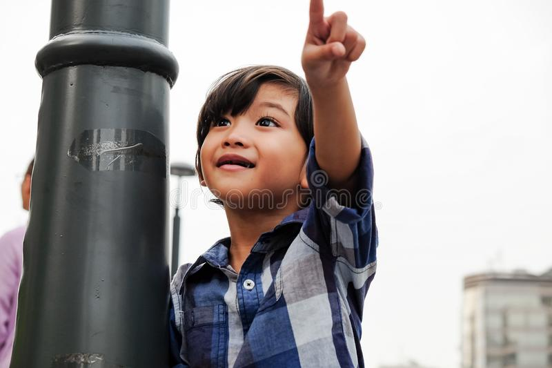Asian Boy Happy Pointing at City Scene Giving Some Direction royalty free stock photos