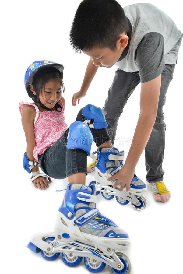 Free Asian Boy Help His Sister Whie Learning Roller Skates On White B Stock Images - 84740684