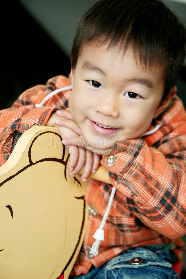 Download Asian Boy Lay On Hobbyhorse Stock Photo - Image: 5113250