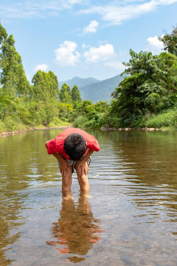 Asian boy looking at fish in a stream. royalty free stock photography