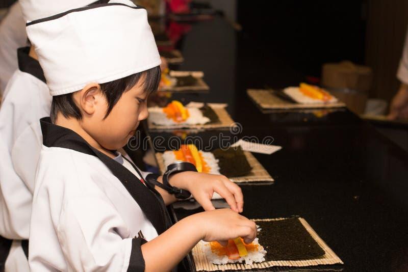 Asian boy making sushi stock photo