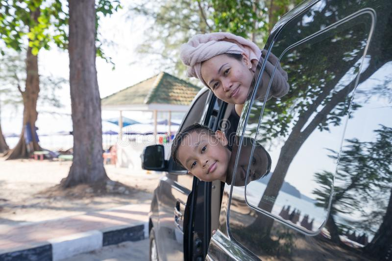 Asian boy and mom extends his face out of the car Which parked by the sea.  stock photos