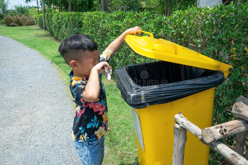 Asian boy is open yellow trash with his left hand and his right hand is holding garbage. Big bin is very bad smell. He is dressed Hawaii blue shirt and jean stock photos