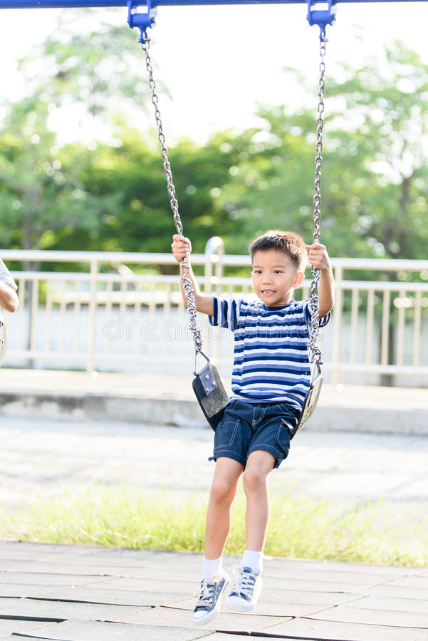 Asian boy play with swinging. with swinging. stock photos
