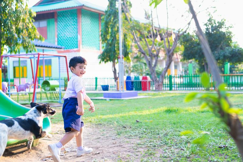 Asian boy playing with his dog in playground under sun light royalty free stock photo
