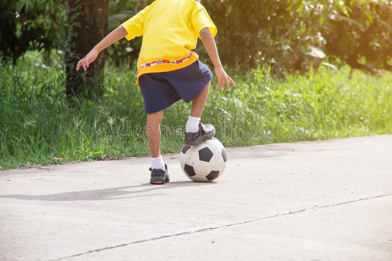 Asian boy playing old football on street,kids are playing soccer royalty free stock image