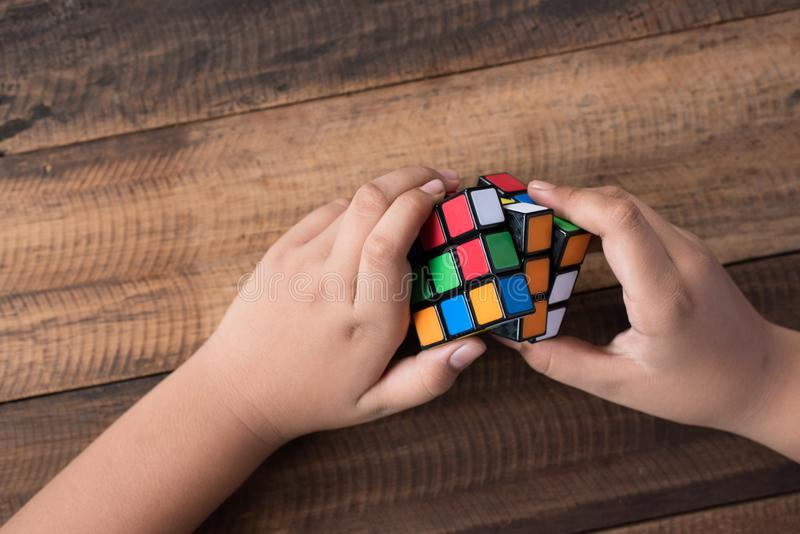 Asian boy playing with rubik`s cube.boy solving puzzle. Brainstorming and brain teaser toy royalty free stock photography