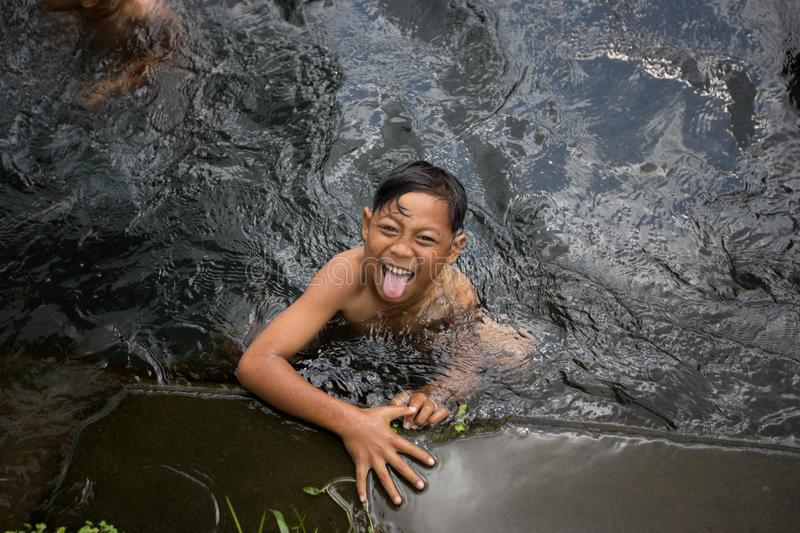 Asian boy playing and swimming in water canal in Bali, Indonesia stock images