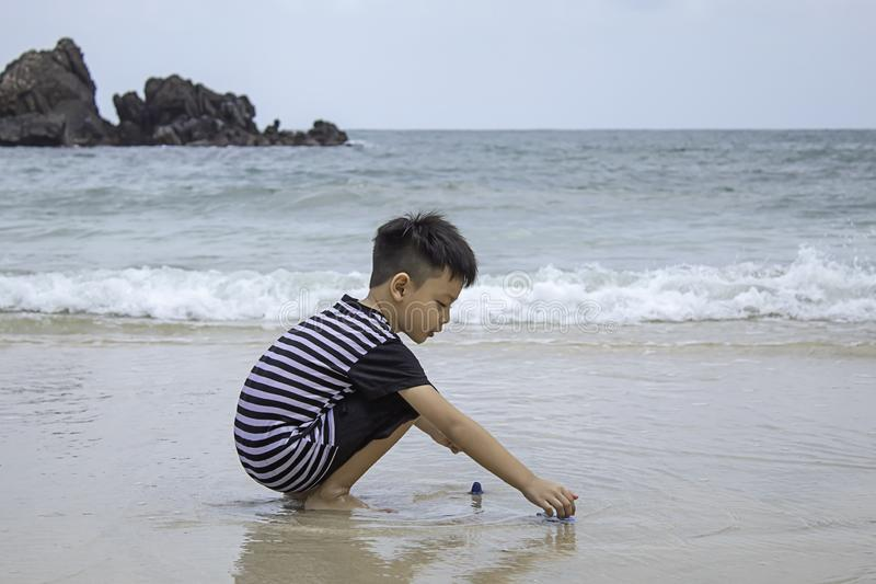 Asian boy playing toy on a sea beach royalty free stock images