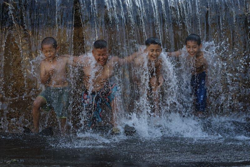 Asian boy playing at waterfall stock photos