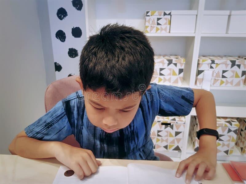 A Boy Reading A Book in the Class Room. Asian Boy Reading A Book in the Class Room royalty free stock photos