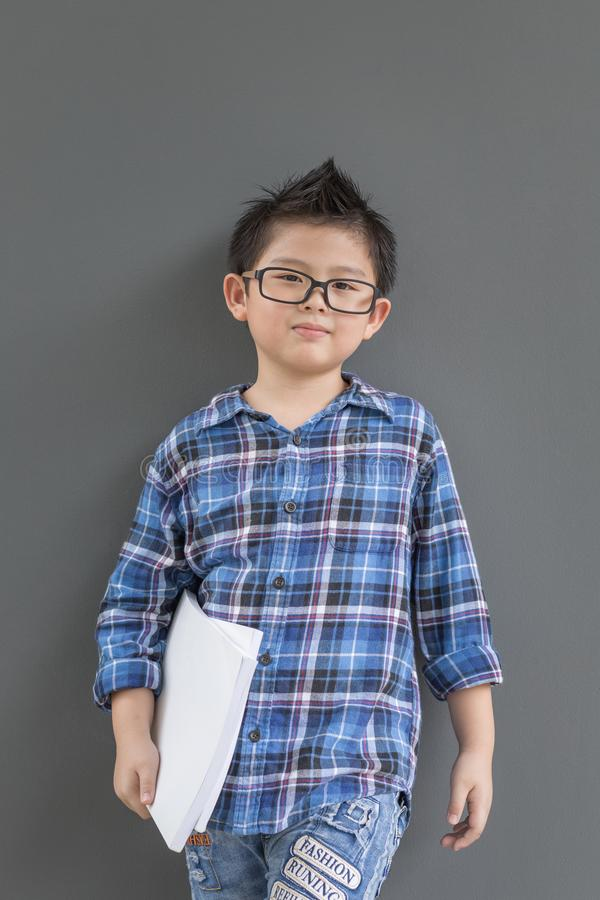 Asian boy ready to go to school and his hands hold the white books. Against the wall royalty free stock photos