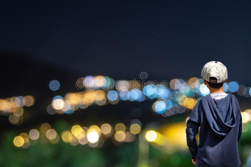 Asian boy see blurred lights of the homes on the mountain royalty free stock image