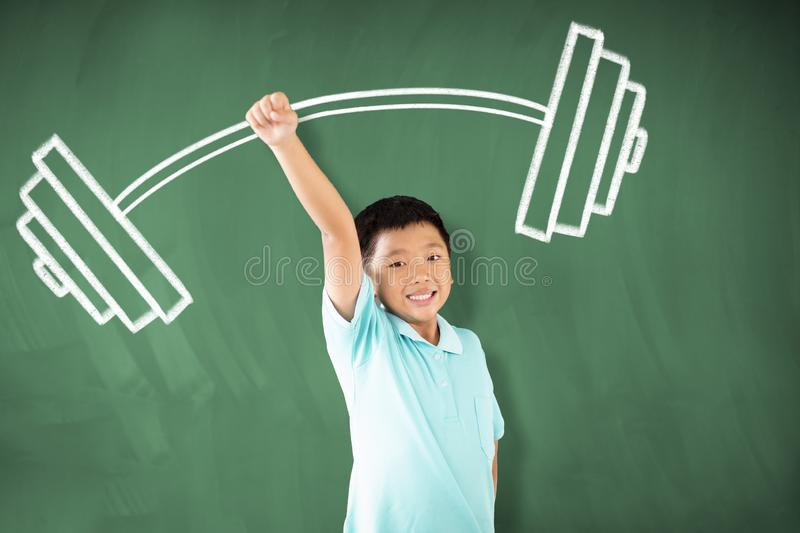 Asian boy standing against chalkboard and  strong winner concept stock image