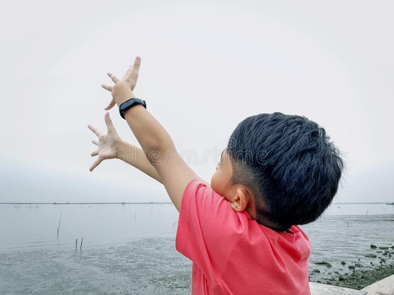 Boy Standing by the Sea Stretching Both Arms Up to Sky stock photos