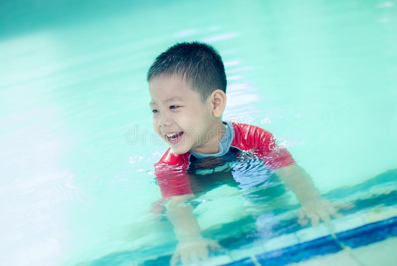 The Asian boy swimming suit has fun at the pool.Portrait of cute little Asian child royalty free stock photography