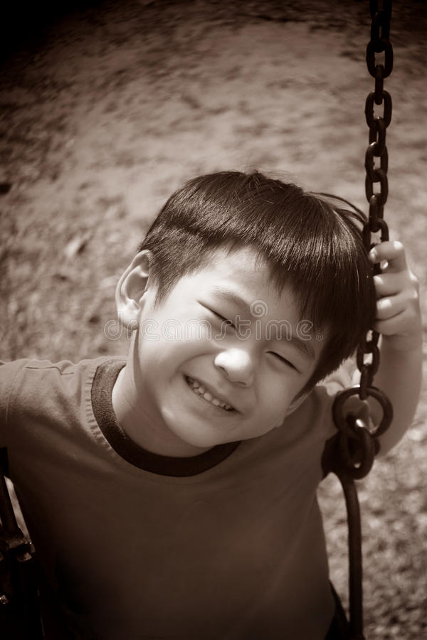 Download Asian boy on a swing stock photo. Image of sunny, playground - 27570004
