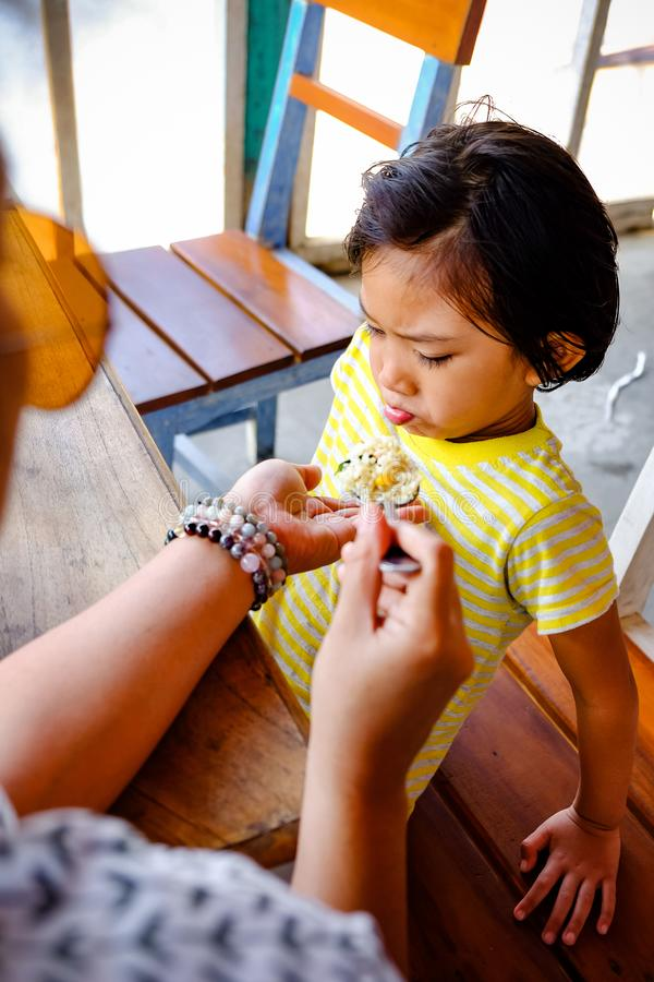 Asian Boy toonde carte faciale expressie terwijl hij voer- en broodmaaltijd was van zijn moeder in een restaurant royalty-vrije stock afbeelding