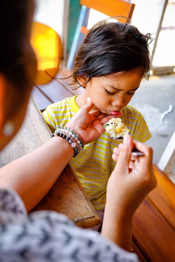 Asian Boy toonde carte faciale expressie terwijl hij voer- en broodmaaltijd was van zijn moeder in een restaurant royalty-vrije stock fotografie