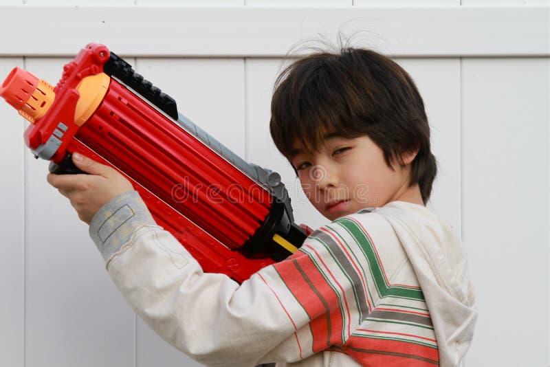 Asian boy with a toy gun stock photos